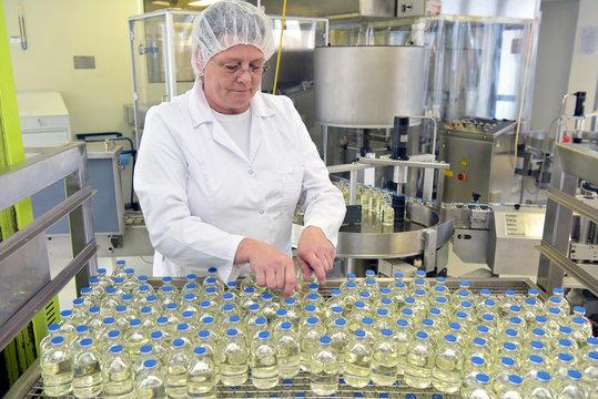 Herstellung von Medikamenten - Frau am Fliessband mit Glasflaschen in einer modernen Pharmaziefabrik // Women on a conveyor belt with glass bottles in a modern pharmacy factory