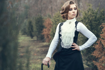 Portrait of gorgeous young woman with elegant Victorian hairstyle wearing old-fashioned gown with jabot leaning on her cane and looking aside, misty autumn park on background. Vintage style Wall mural