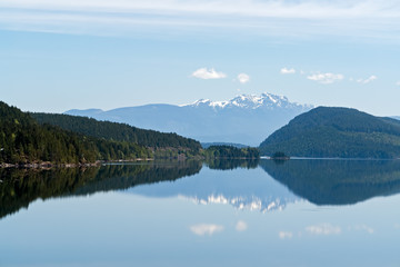 Snowy mountains reflection in a lake - Vancouver island, BC, Canada