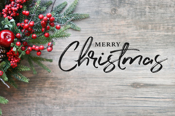 Merry Christmas Text with Christmas Evergreen Branches and Berries in Corner Over Rustic Wooden Background Wall mural