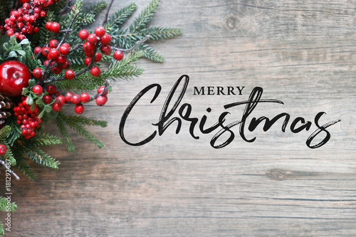 Merry Christmas Text With Evergreen Branches And Berries In Corner Over Rustic Wooden Background