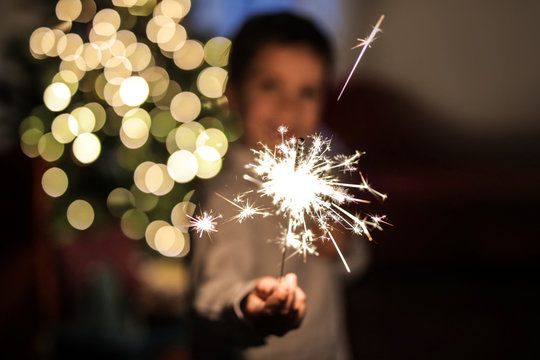 Child holding a small firework