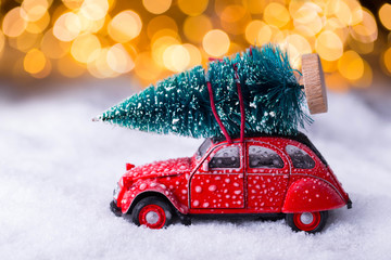 Oldtimer car is carrying a christmas tree through beautiful winter landscape
