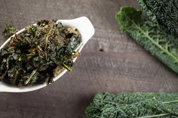 Freshly baked green kale chips prepared with olive oil on dark wooden background above shot