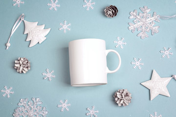 White coffee mug  with Christmas decorations on blue background. Space for text or design.