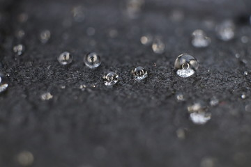 Little water drops on black leather background texture. Macro Closeup.