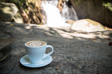 coffee on stone with blur waterfall background