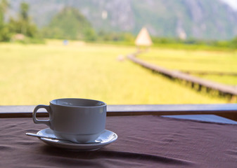 coffee cup with blur rice field background
