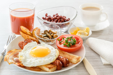 Full English breakfast with smoked sausages, fried egg, bacon, tomato, toast and beans. Tea with milk. A glass of fresh juice. Cutlery. Breakfast on a white plate on a light background. soft light