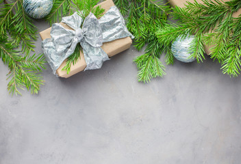 Christmas background in gray-blue colors with gifts wrapped in kraft paper, with ribbons, with glass Christmas-tree balls and xmas tree. Flat lay, top view