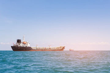 Transport cargo ship over seacoast skyline with clear blue sky background