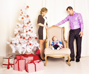 Happy parents with baby in decorated room for Christmas