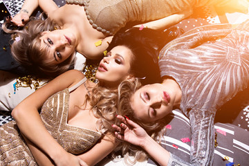 Top view of three best friends tell secrets in bed . Group of pretty young women in evening dresseslie on back and have fun.