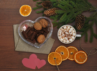 Coffee with marshmallow, chocolate, nuts and spruce branches on a wooden table. View from above. Christmas and New Year. Still life