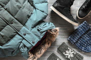 Women's warm winter clothing and accessories - jacket, black leather high top sneakers, gloves and hat. Wish list or shopping overview concept.  Fashion concept. View from above. Flat lay