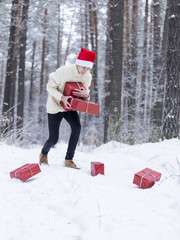 teenager in hat Santa Claus collects gifts in a snowy forest in the snow, red boxes with gifts.