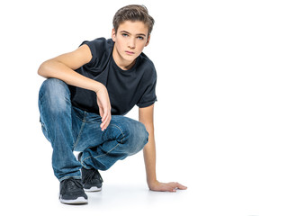 Photo of teenage handsome guy posing at studio