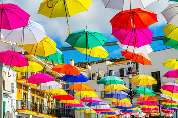 Colourful umbrellas urban street decoration. Hanging colorful umbrellas over blue sky, tourist attraction
