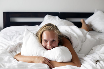Morning time. Young beautiful and happy woman lies in bed.