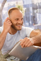 Handsome man with earbuds and tablet
