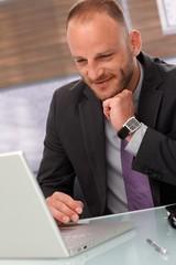 Happy businessman using laptop