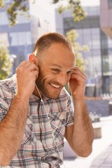 Happy man putting in earbuds