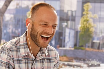 Happy man laughing with earbuds
