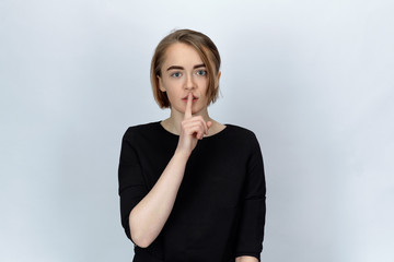 Studio portrait on isolated background of a young attractive woman with wide open eyes, holding a finger to call for silence