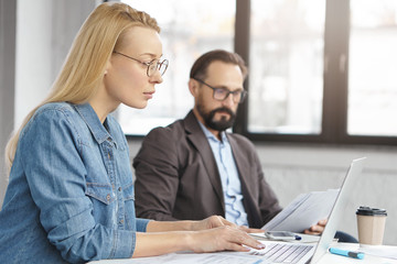 Serious blonde woman in denim shirt looks attentively into screen of laptop, busy with making financial report and her bearded colleague reads documents, checks database, creats account, do paperwork