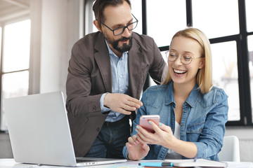 Portrait of happy woman shows funny photos to her male colleague, have minute rest, surrounded with laptop and papers, create new innovative strategy, have good mood. People and technology concept