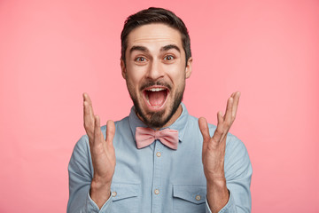 Excited bearded man in formal festive clothes happy that friends came on party, raises hands with enjoyment, glad to recieve congratulations and presents, celebrates special event in his life