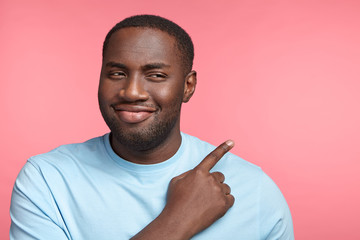 Young dark skinned plump man has intriguing and cheerful expression, indicates with fore finger at copy space, says: Just look at this! Unshaven young African American man poses in pink studio