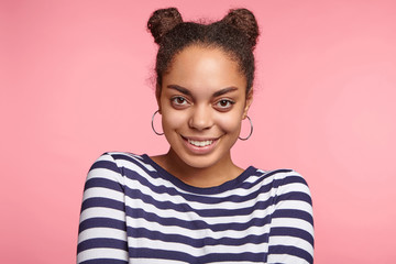 Happy African American young woman with hair knots, wears round earrings, looks directly into camera, to meet international friends, isolated over pink background. People and happiness concept
