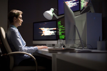 Portrait shot of concentrated middle-aged software developer wrapped up in work while sitting in front of computer at dim office