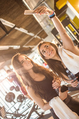 Two beautiful smiling girls taking selfie photo on smartphone in the gym.