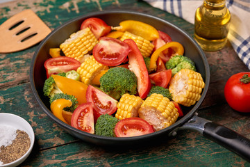 Fresh fruits and vegetables on a frying pan on an old wood background