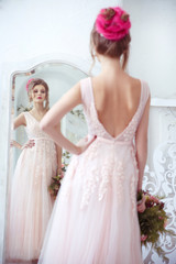 Elegant bride with a bouquet in hand in front of the mirror view from the back.