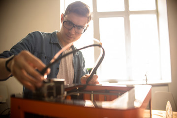 Waist-up portrait of concentrated young technician in eyeglasses repairing 3D printer after breakage, interior of spacious laboratory on background