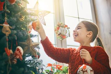 girl is decorating Christmas tree
