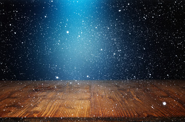 Night sky with snowfall and wooden stage