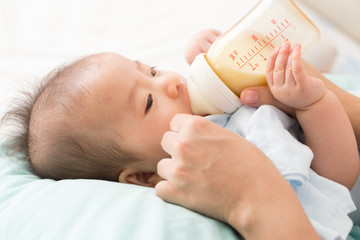 Hand of mother feeding baby with milk bottle