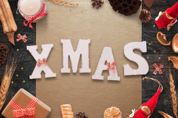 Xmas white wooden text on wooden table surrounded with Christmas decorations.