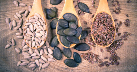Flaxseed, pumpkin and sunflower seeds in wooden spoons.