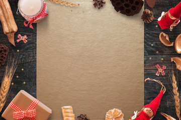 Christmas scene with Christmas decorations on gold table cloth and black wooden table. Free space for text.
