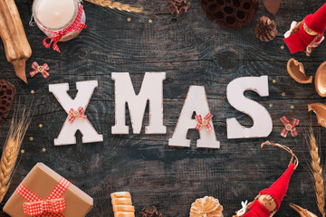 Xmax text on black wooden table with Christmas decorations, gift, candle, doll, stars, and bows.