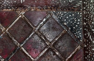 Close-up squares on old rusty metal surface and black painted stripes in top right corner.