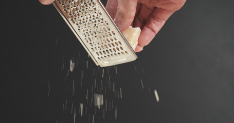 closeup of grating aged parmesan over dark background