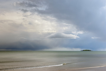 Capel island in Scotish Sea as seen from Youghal beach County Cork in Ireland on a dull day with calm waters and distant stormy skies