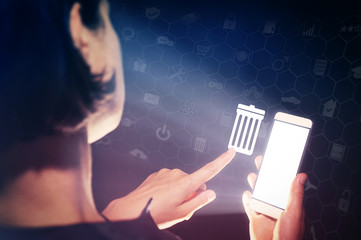 Image of a girl with a smartphone in hands. She presses on the trash can icon. The concept of deleting files, contacts, putting in order, cleaning service etc.