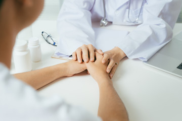 Friendly female doctor hands holding patient hand sitting at the desk